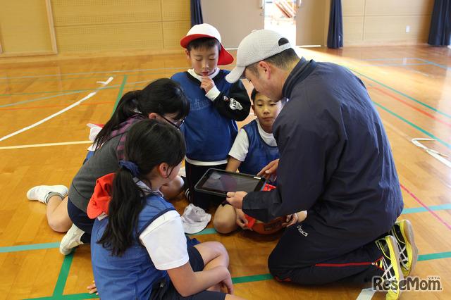 2018年1月26日、佐賀県多久市立東原庠舎中央小学校で行われた公開授業のようす(写真は体育の時間)シュートとパスの回数を記録しておき、試合後の作戦会議に役立てる。先生はアドバイス係