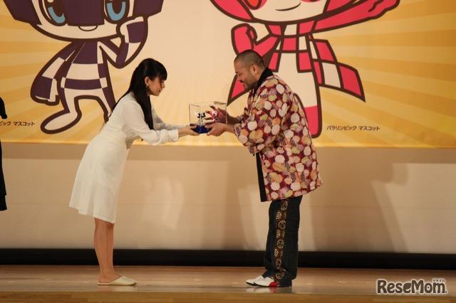 キャラクターをデザインした谷村亮氏と審査会の中川翔子(しょこたん)委員。キャラクターのフィギュアが授与された