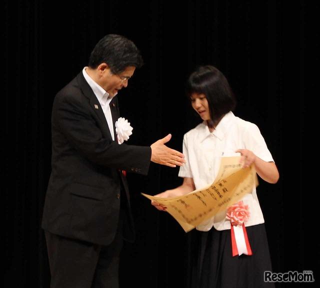 石井大臣から「おめでとう」という言葉とともに握手を求められた、最優秀賞受賞の井崎英里さん