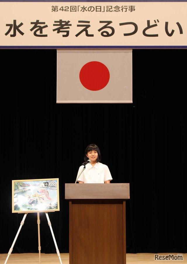 朗読中の井崎英里さん。横には、自身が描いた絵が飾られている