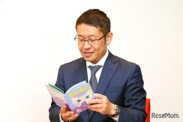 「ほんのハッピーセット」の第2弾の絵本「ねんねこ」を手に取る小川大介氏