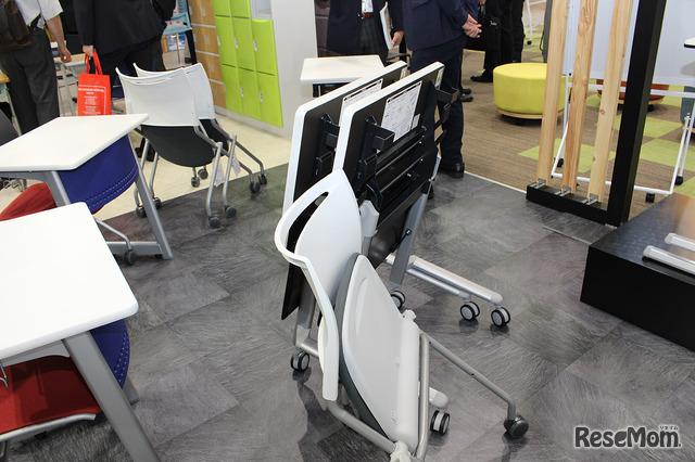 片付けやすい机と椅子。赤い椅子と対になっている左の机にはキャスターが付いていないように見えるが、天板下のレバーを持ち上げるとキャスターが出てくる。