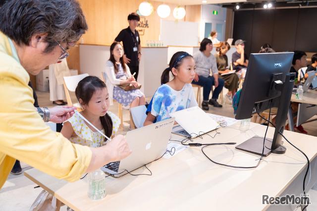 目と画面の距離を測る綾木先生。ノートパソコンでの作業の場合、その距離は25cmと若干近め