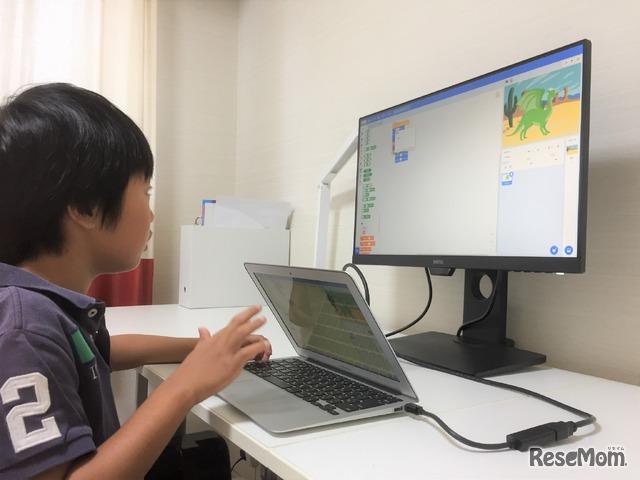 プログラミング体験会で作ったゲームの続きを楽しむ息子。画面を眺める時間は長いが、目にやさしいアイケアモニターなら安心だ