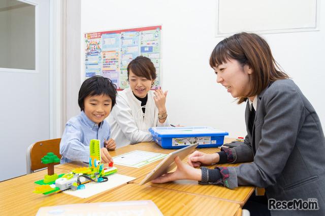 体験授業では保護者は隣で説明を聞きながら子どものようすを見学できる「ワニの口に赤いブロックを入れると…」